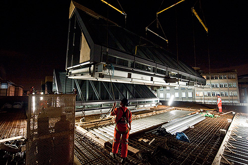 The section is gently lowered into place on the roof of the new station building. The crane driver is blind at this point and the whole operation is guided by a skilled banksman.