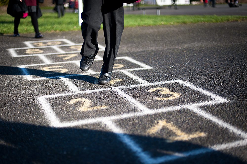 primary school children play the classic payground game hopscotch