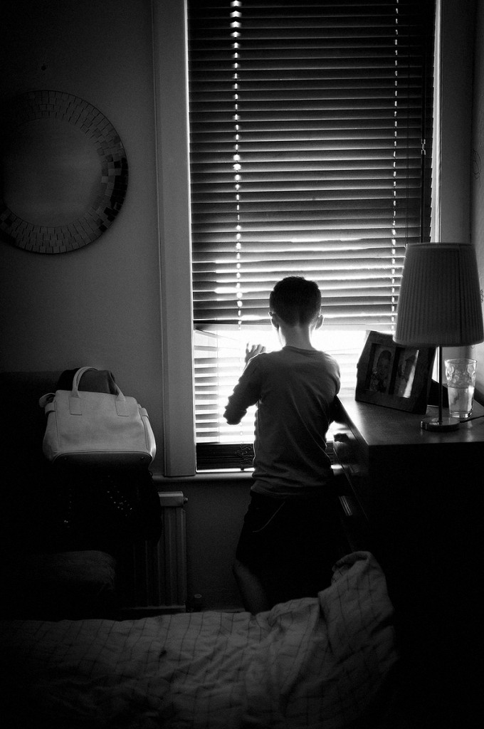 A boy watches the goings on from his parents' window