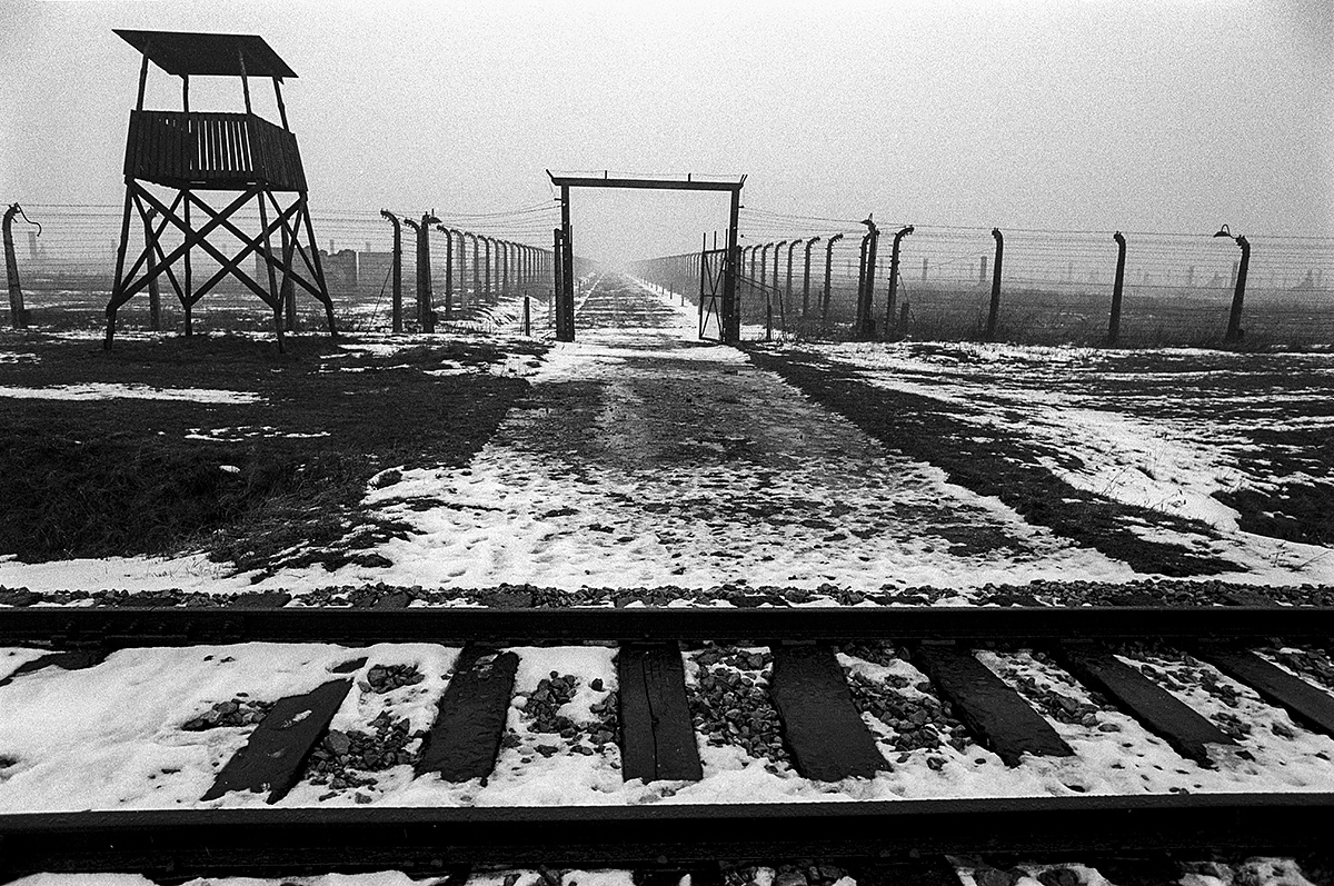 Watchtower, tracks and endless fences. Brzezinka (Birkenau). Auschwitz. Photo: © Michael Cockerham 1993.