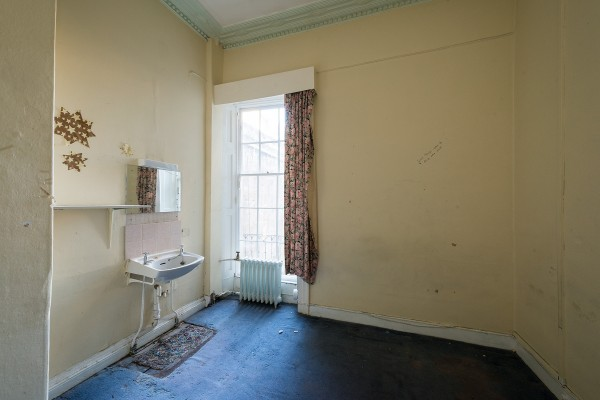 Derelict room with sink and faded carpet